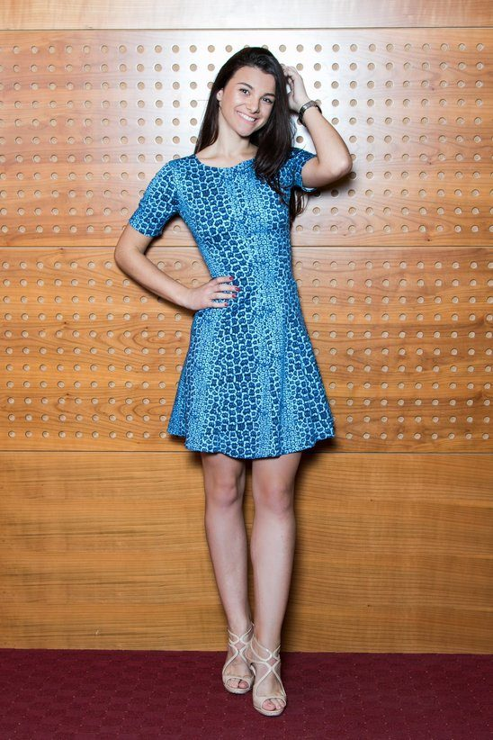 Happy girl is smiling, while posing in an A-shape dress. This elegant african inspired dress has a blue crocodile print and a short sleeve.