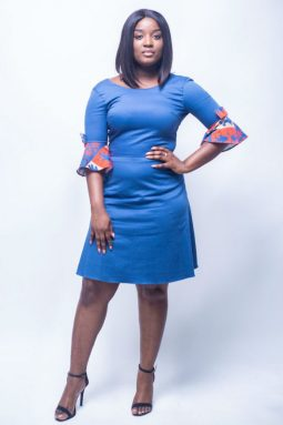 Black woman looks seriously, while posing with an A-shape dress. That african inspired dress is Plain Blue. It has a sleeve with bow-tie and red decoration.