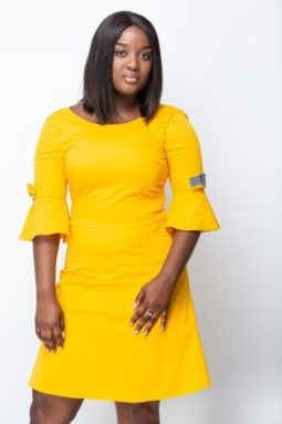 Black woman poses with an A-shape dress. It is plain yellow and has a sleeve with bow-tie.