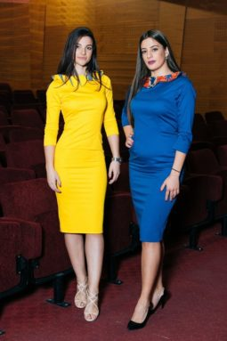Two woman showing their form-fitting dresses, one plain yellow and the other blue