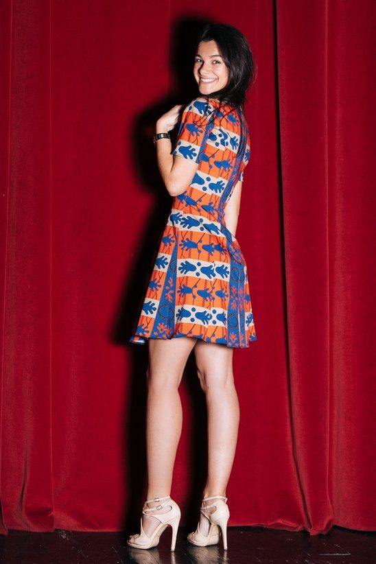 Woman poses in front of a red curtain in a form-fitting dress which is called Red & Blue.