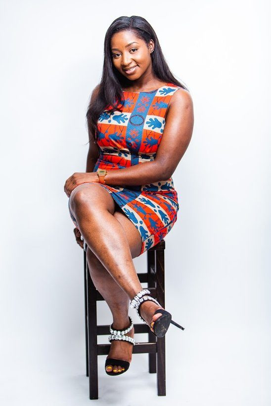 Black woman sits on a chair in a form-fitting dress called Red & Blue. It has a belt and no sleeve.