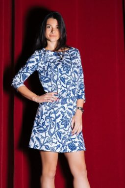 Woman poses in a tunic dress called Blue & White Floral, in front of a red curtain.